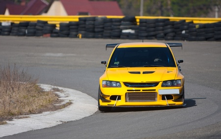 race track: Yellow racecar on road