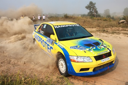 sponsors: Ukraine. Kiev. The fifth stage of the championship of Ukraine Alexandrov Rally - 15.08.2010. Command T. Kravtsova and N. Sobolev on the Mitsubishi Evo 8. The race in difficult conditions, very hot and dusty. The red car is goes along a dusty road.