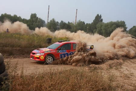 rally car: Ukraine. Kiev - August 15, 2010. The 5-th stage of the championship of Ukraine Alexandrov Rally:  Salyuk Alexander, Jr. and Evgeniy Chervonenko drives their Mitsubishi Evo 9. The race in difficult conditions, very hot and dusty.