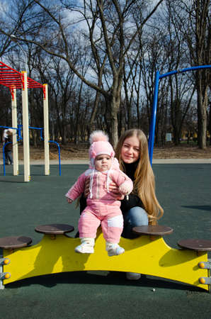 Mom plays on a bright playground with a small child in the street, nomads, a house during the day