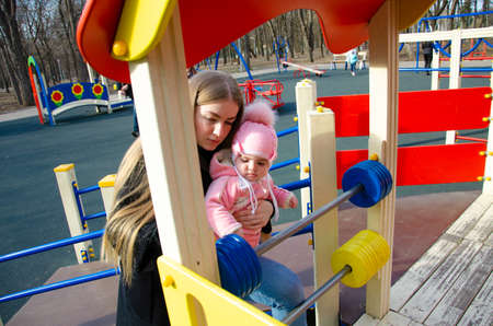 Mom plays on a bright playground with a small child in the street, nomads, a house during the day Stock Photo