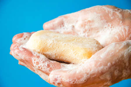 Women's hands are holding soap. Soap foam on the hands. Yellow soap in the hands. Woman washes soap with hands side view on a blue background. Virus protection. COVID-19