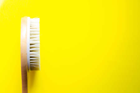 Dry massage. Brush made of natural cactus bristles, animals. Massage brush on a yellow background from different angles. Place for text. Macro brush. Copy Space Handle anti-cellulite brush.