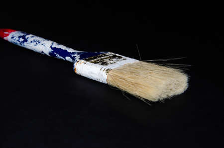 Used paint brush. Blue brush with a red tip in white paint. Macro photo. Repair brush in hand. Fibers Copy Space