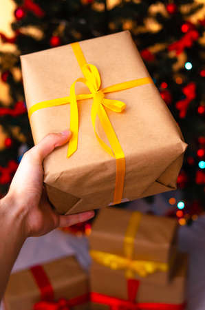 Boxes with gifts on a light, blue background and under the Christmas tree. Gift in the hand. Christmas presents, Nicholas Day, Valentine's Day. Bright boxes with bright ribbons. Gifts in Macro