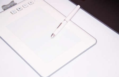 White graphics tablet on a white background. The work of a graphic designer. View of the top, side view. Tablet in macro. Pen stylus for drawing. Buttons on the tablet.