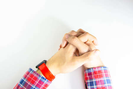 Male hands forearm, on a white table first-person view. Squeeze, hold, consider, demonstrate. Hands that demonstrate, control, dominate, gesticulate. CopySpace Copy space