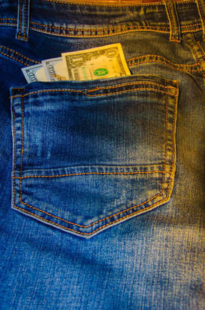 American banknotes in jeans pocket. A note in denominations of $ 100 peeps, stick out from the back, the foremost pants pocket. Money falls out of pocket. Flare effect. View from different angles