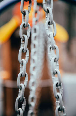 Metal chains with a large ring for a children's swing on the street in macro