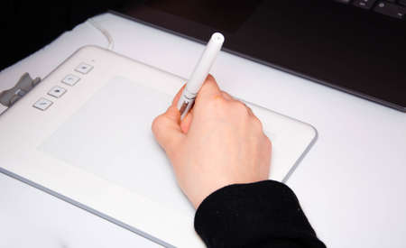 Female hands work on a graphic tablet. Hand holds stylus pen and draws. White graphic tablet. The work of a graphic designer. Girl works on a tablet connected to a laptop. Rear view from behind