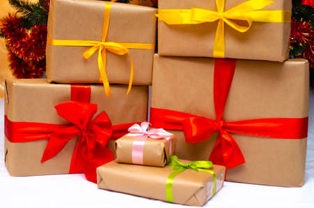 Boxes with gifts on a light, blue background and under the Christmas tree. Gift in the hand. Christmas presents, Nicholas Day, Valentine's Day. Bright boxes with bright ribbons. Gifts in Macro Stock Photo