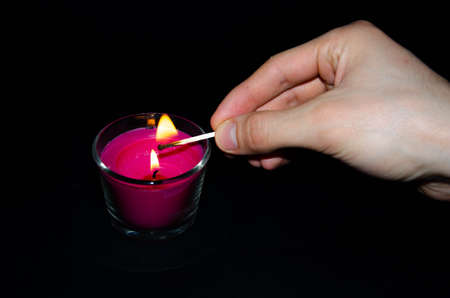Bright pink candle in a glass jar on a black background. The candle is burning. Redeemed. A hand sets fire to a candle with matches. Put out the candle with your fingers, hands. 写真素材