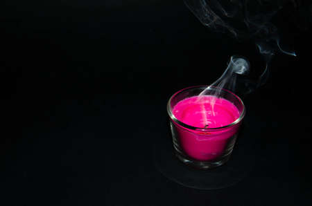 Bright pink candle in a glass jar on a black background. The candle is burning. Extinguished candle. Smoke from the candle. Hearth of fire. Tongue of flame. Macro.