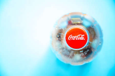March 2020. Kramatorsk, Ukraine. 1 liter Coca-Cola empty plastic bottle. Top view. Coca cola cap in close-up on blue and yellow background.  copy space