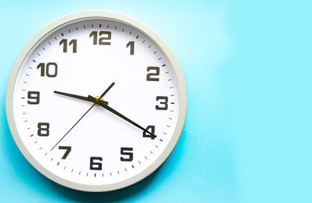 Analog white clock on a blue background. Large numbers and arrows. Clock in close-up. Place for text. Business, are you ready?