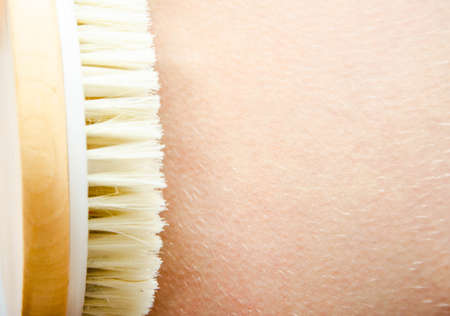 Dry massage. Massage at home, in the salon with a brush of natural bristles. Girl does massage legs, in close-up