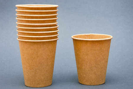 A brown paper cup for coffee, tea, a drink made from environmental materials. A stack of glasses stuck in one in one stand next to one cup on a white, black and yellow background