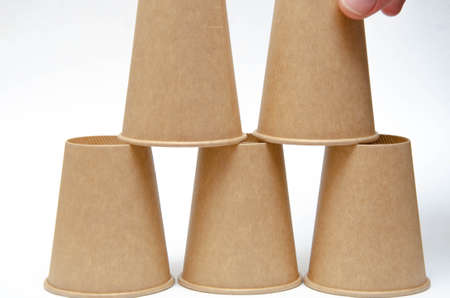 Brown paper cup for coffee, tea, a drink from environmental materials on a white background. The male hand builds a pyramid of cups in macro and overall plan. Place for text on the left and right.