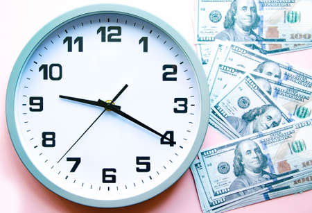 Analog white clock and dollars on a gray, yellow, blue background. Banknotes next to the clock, on top. Place for text. Business, are you ready? Copy Space Banco de Imagens