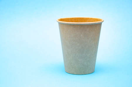 Brown paper cup for coffee, tea, a drink from environmental materials on a blue background. A small cup in macro is on the right. Front view and top view, bottom visible. Place for text on the left