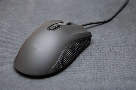Black gaming mouse with side extra keys and a matte finish on a black background. A mouse from different angles is a general plan and macro side keys and main ones. Surface as a weave, mat and mouse for games