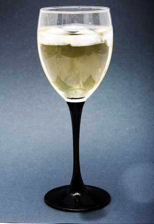 A glass of white wine with pieces, ice cubes. Wine with ice on a black background. Glass with a black leg