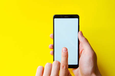 A male hand holds a smartphone, points a finger, types. Communication on a smartphone, correspondence. Place for text. Smartphone in hand on a yellow background.