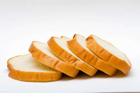 Bread. Long loaf sliced, sliced, sliced on a white background. Bread in macro, stacked on top of one another. Slices of loaf Foto de archivo