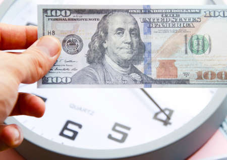 Analog white clock and dollars on a blue background. A man's hand holds notes of 100 dollars on a background of watches. Banknotes next to the clock, on top. Place for text. Business, are you ready? Banco de Imagens