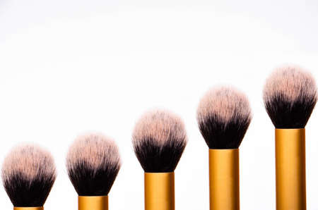 Large fluffy makeup brush with gold pen and black edge. The tips of the upper part of the brush from the bottom in a row are the same and in the form of a step, a pedestal, a podium from makeup brushes 版權商用圖片 - 148164586