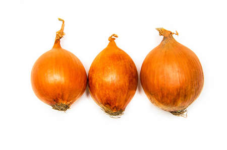 Three large onions lie in a row on a white background. Onions in macro. Different sized onions