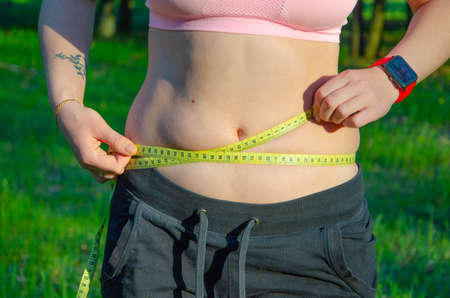 The girl measures her waist, a whirlpool with a yellow centimeter. Fat belly, folds of fat. Sports, proper nutrition, weight loss.