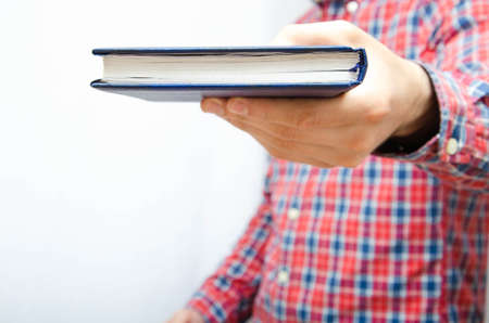 Young man in a plaid shirt with a smartphone on a white background. The guy holds the notebook in front of him, focus on the notebook. Hand holds out a book, notepad