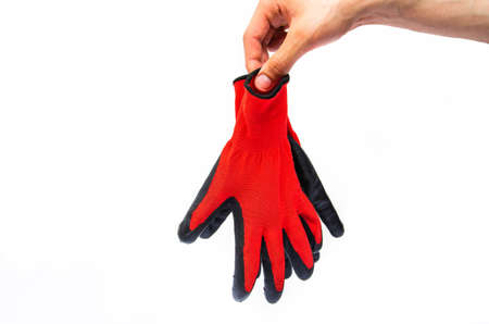 Gloves for workers, construction red with black rubber coating. Black-red gloves. Hand holds, throws out gloves on a white background. Used gloves