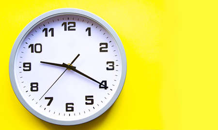 Analog white clock on a yellow background. Large numbers and arrows. Clock in close-up. Place for text. Business, are you ready?