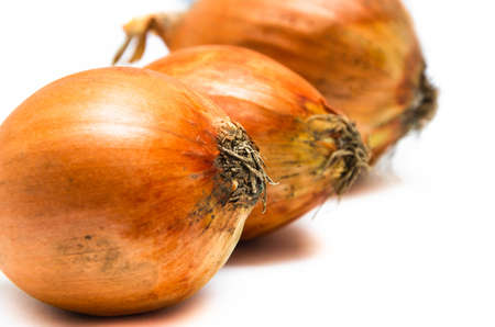 Three large onions lie in a row on a white background. Onions in macro go into the distance. Different-sized onions 版權商用圖片 - 148167622