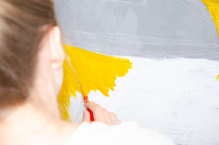 Young girl designer draws a city drawing with paints on a gray wall Imagens