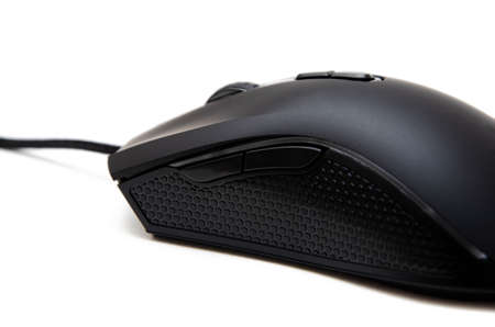 Black gaming mouse with side extra keys and a matte finish on white background. Mouse side view in macro and general plan. Lateral rubber inserts against sliding, pimples. Left and right mouse