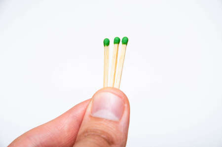 Wooden little matches with a green head. The male hand holds three matches in the hand evenly and at an angle, first-person view Stock Photo