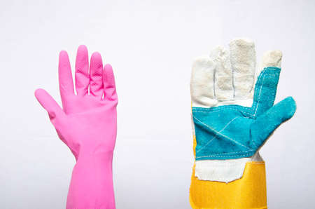 Pink rubber glove for cleaning with the palm up and next to the construction glove with the palm up on a white background. Men vs women. Equality. Gloves hold each other