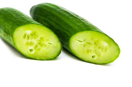 Two greenhouse green cucumbers on a white background are cut at an acute angle. Fresh cucumbers in a cut. Cucumbers in macro