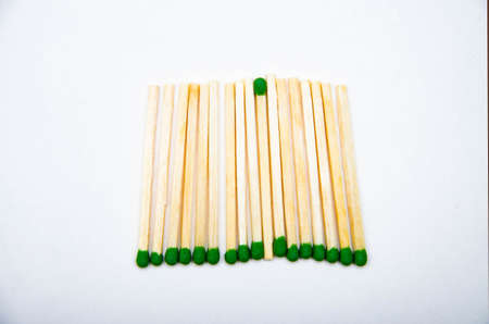 Wooden little matches with a green head. A bunch of matches lie in the middle view of the spread, bottom and top
