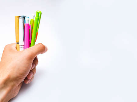 A large pile of a number of ballpoint pens of different colors on a white background in a bunch of male hands. Pens for writing in close-up on a white background