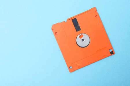 Floppy orange 3.5 on a blue background. Floppy disk general plan and close-up.