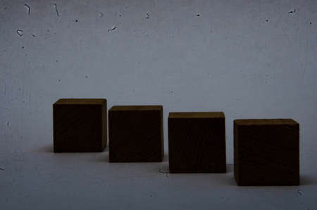 Wooden cubes on a white background. Four identical cubes lie, stand in a row together and separately, directly and at an angle. Cubes in the dark Reklamní fotografie