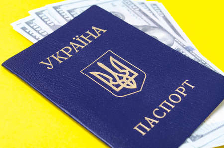 Ukrainian passport on a yellow background. $ 100 dollars are inside the passport at different angles