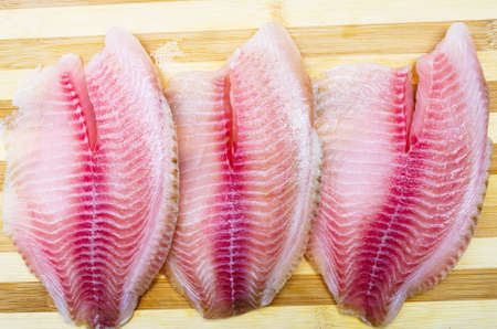 Three filet fish hare, rabbit fish on a cutting board in macro. Dorado fillet, telapia. Raw fish, seafood in macro Archivio Fotografico