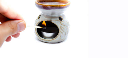 Aroma lamp on a white background. Lamp with aromatic oils on a white background. A man's hand sets a candle in an aroma lamp
