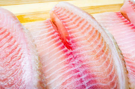 Two filet fish hare, rabbit fish on a cutting board in macro. Dorado fillet, telapia. Raw fish, seafood in macro. Top and side view Stock Photo