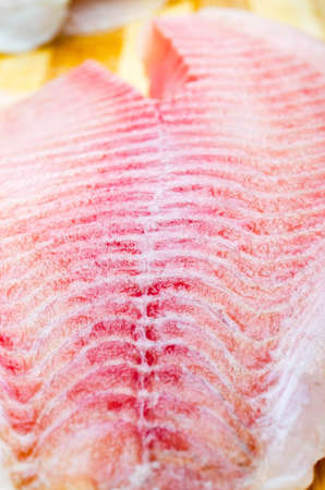 One filet of hare fish, rabbit fish on a cutting board in macro. Dorado fillet, telapia. Raw fish, seafood in macro. Top and side view. Large approximation of filet